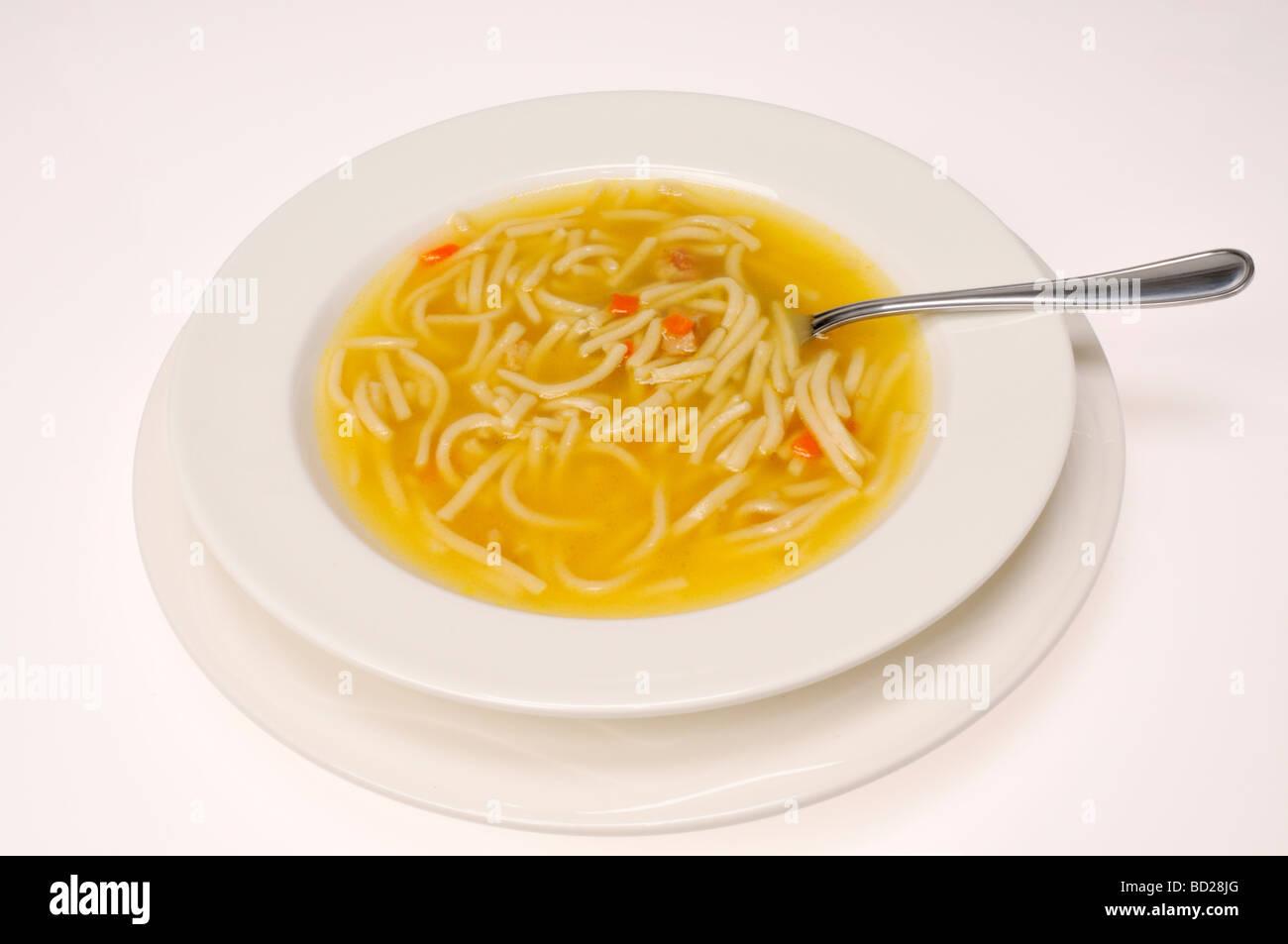 Bol de soupe poulet et nouilles avec cuillère sur fond blanc. Photo Stock