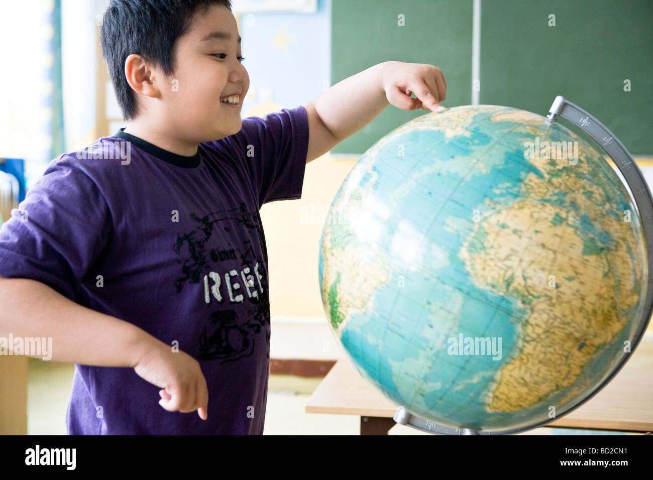 Boy looking at globe en classe Photo Stock