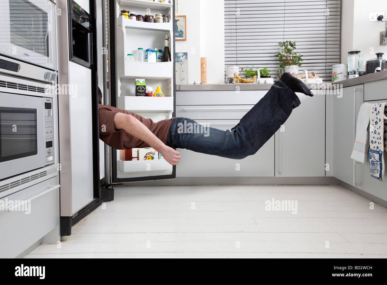 L'homme à la recherche dans un réfrigérateur Photo Stock