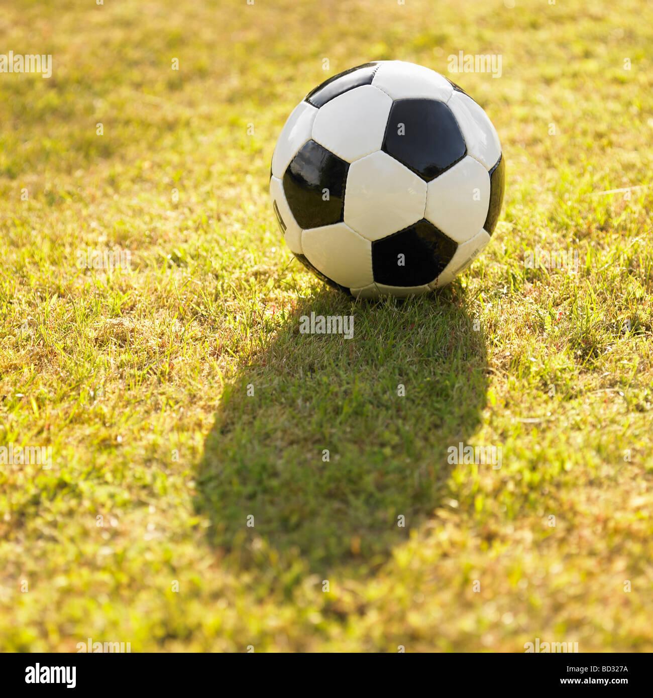 Noir et blanc en cuir générique / football ballon de football sur gazon, éclairé au soleil. Photo Stock