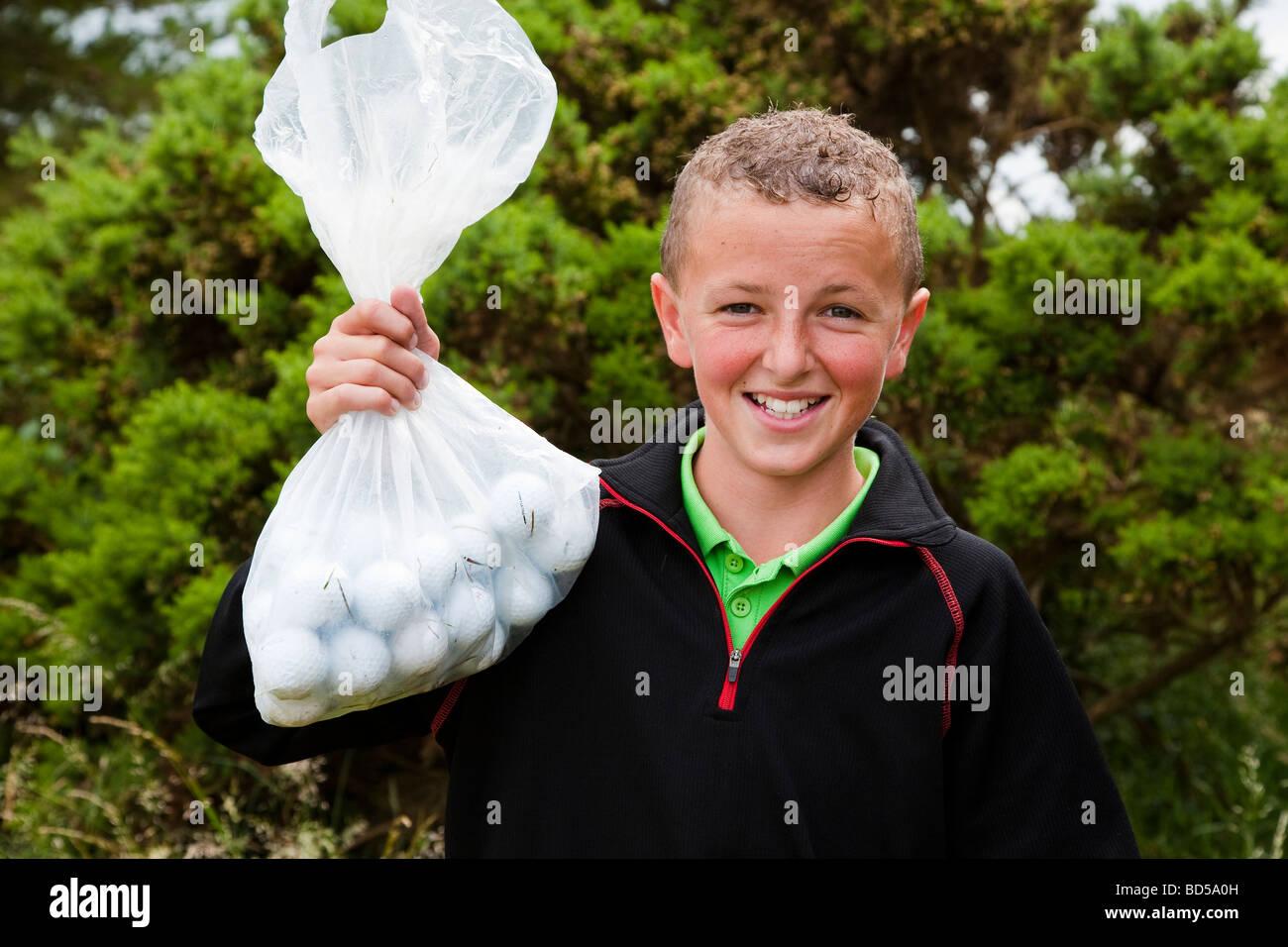 Jeune garçon la collecte des balles de golf sur un parcours de golf Photo Stock