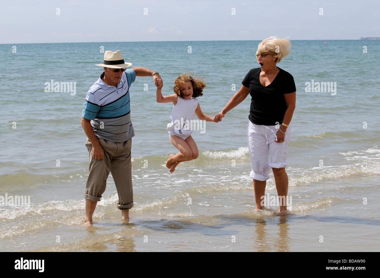 Les grands-parents jouer avec vos petits-enfants à la mer sauter et danser dans la mer Banque D'Images