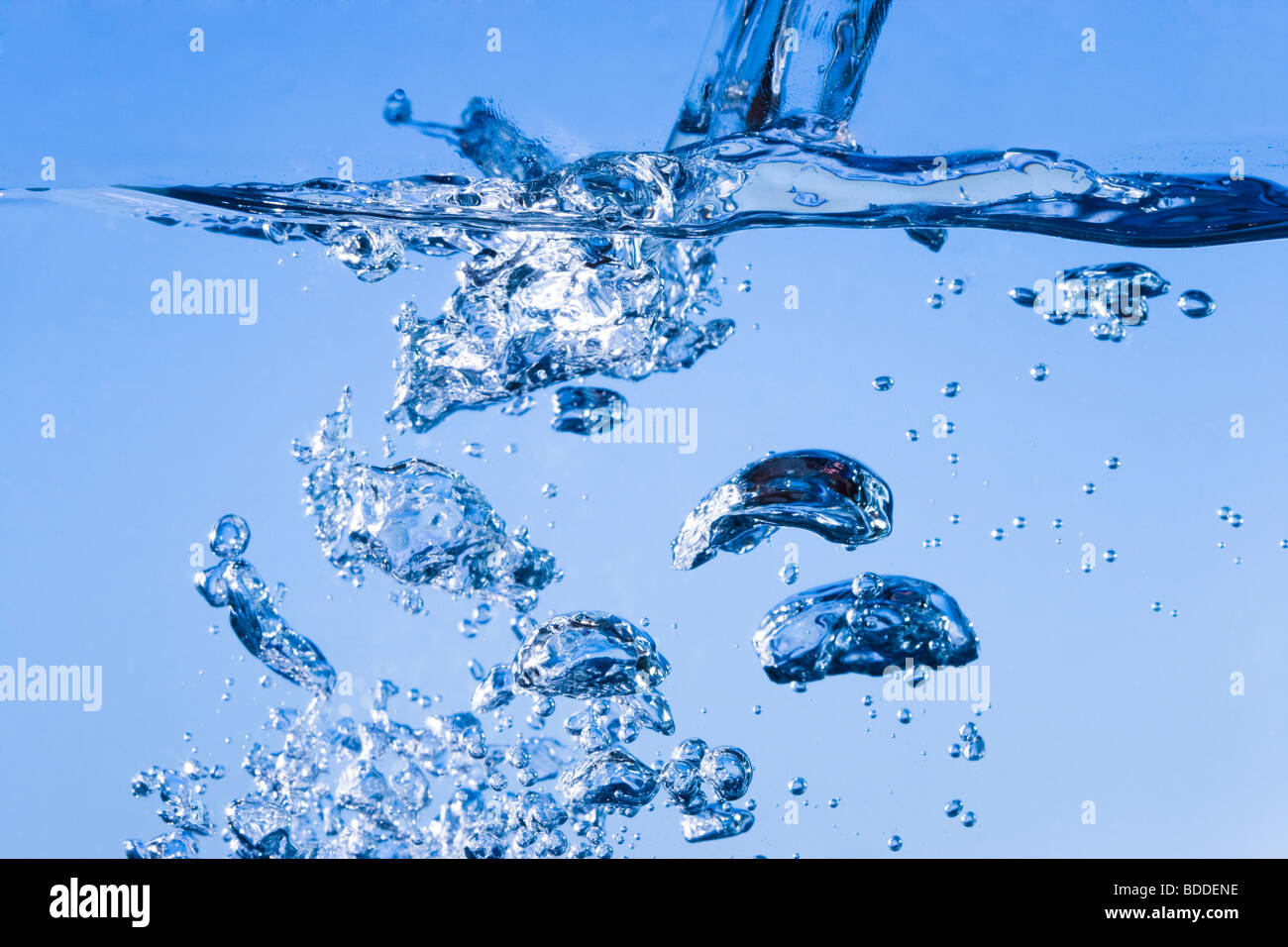 Verser de l'eau créant des bulles sous la surface Photo Stock