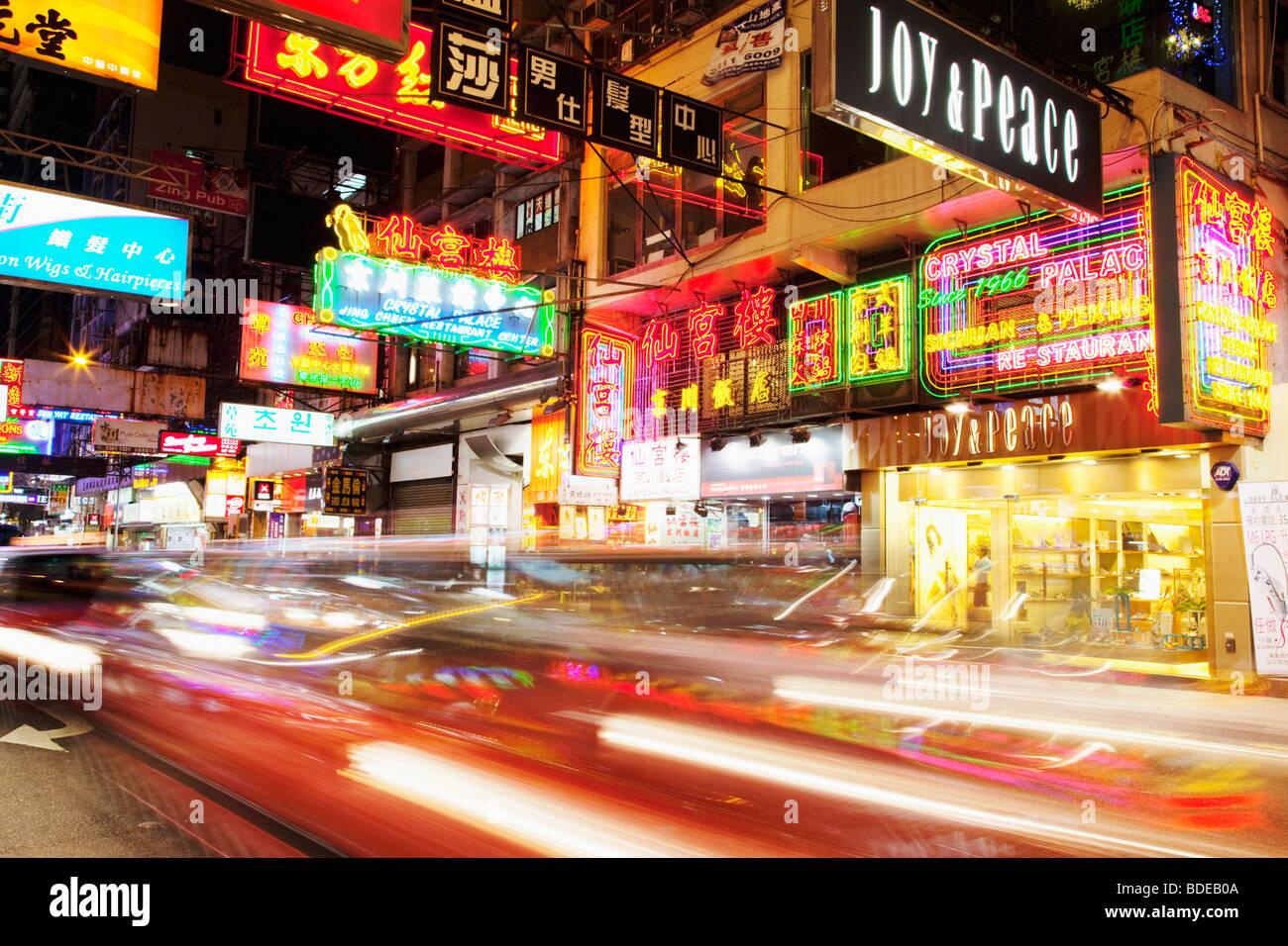 Enseignes au néon et lumière voiture trail à Tsim Sha Tsui, Kowloon, Hong Kong, Chine. Photo Stock