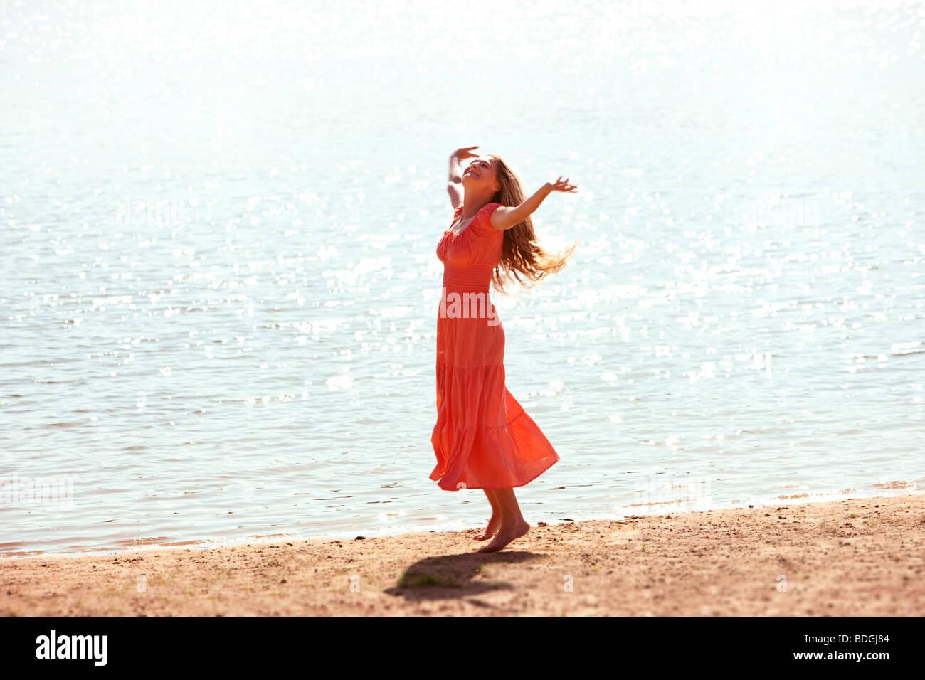 Femme dansant sur une plage avec l'abandon, les bras tendus. Photo Stock