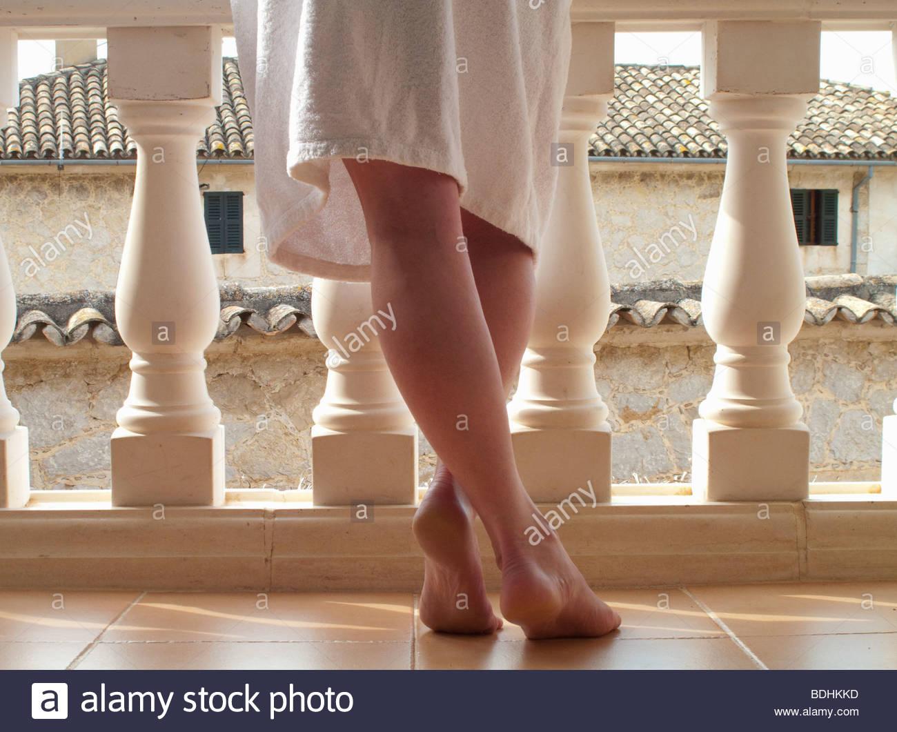 Les pieds nus de femme en peignoir à balustrade balcon Photo Stock