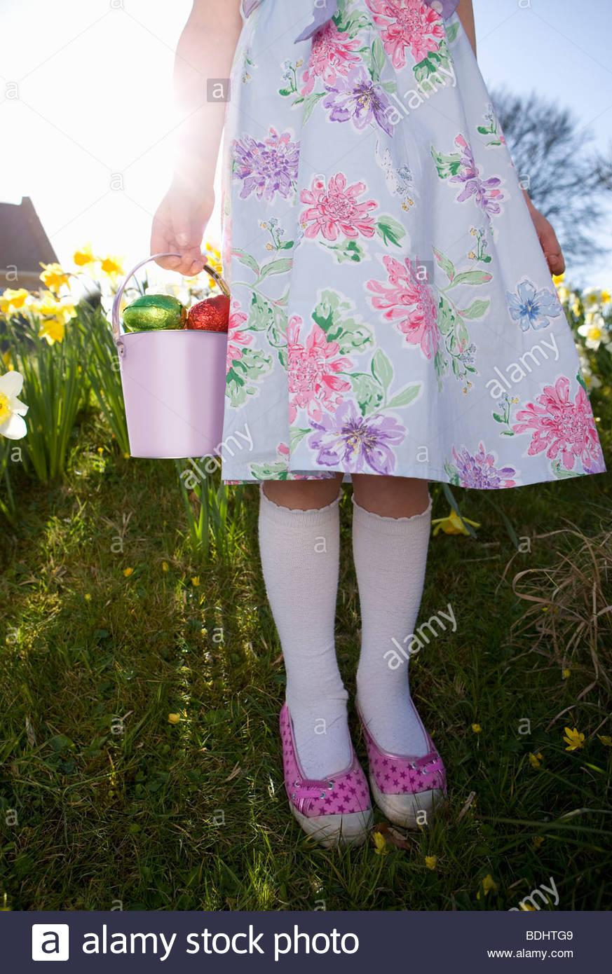 Girl trouver des oeufs de Pâques en chocolat dans les fleurs Photo Stock