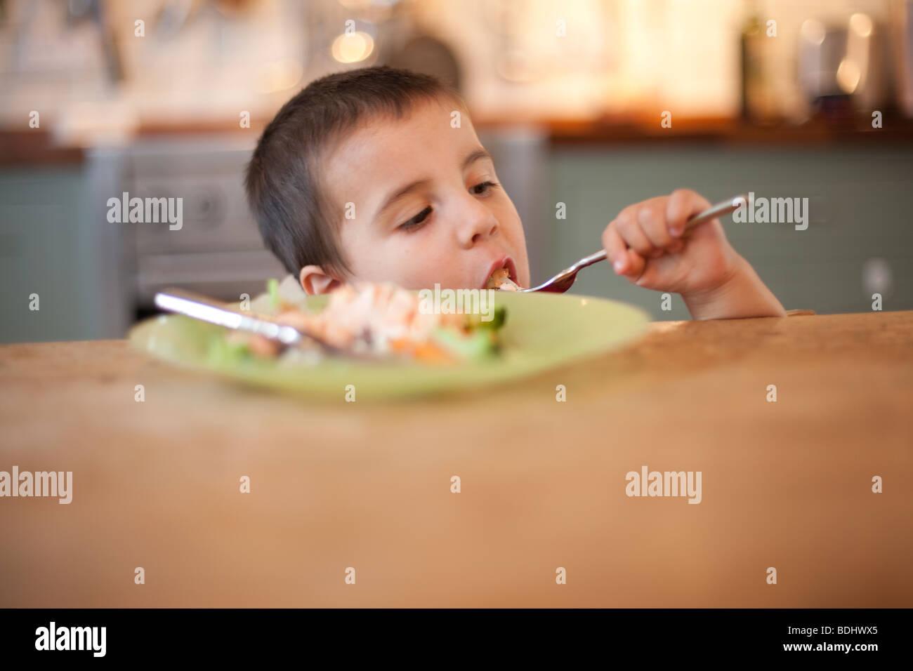 3 ans du mal à manger de son assiette à la table de cuisine Banque D'Images
