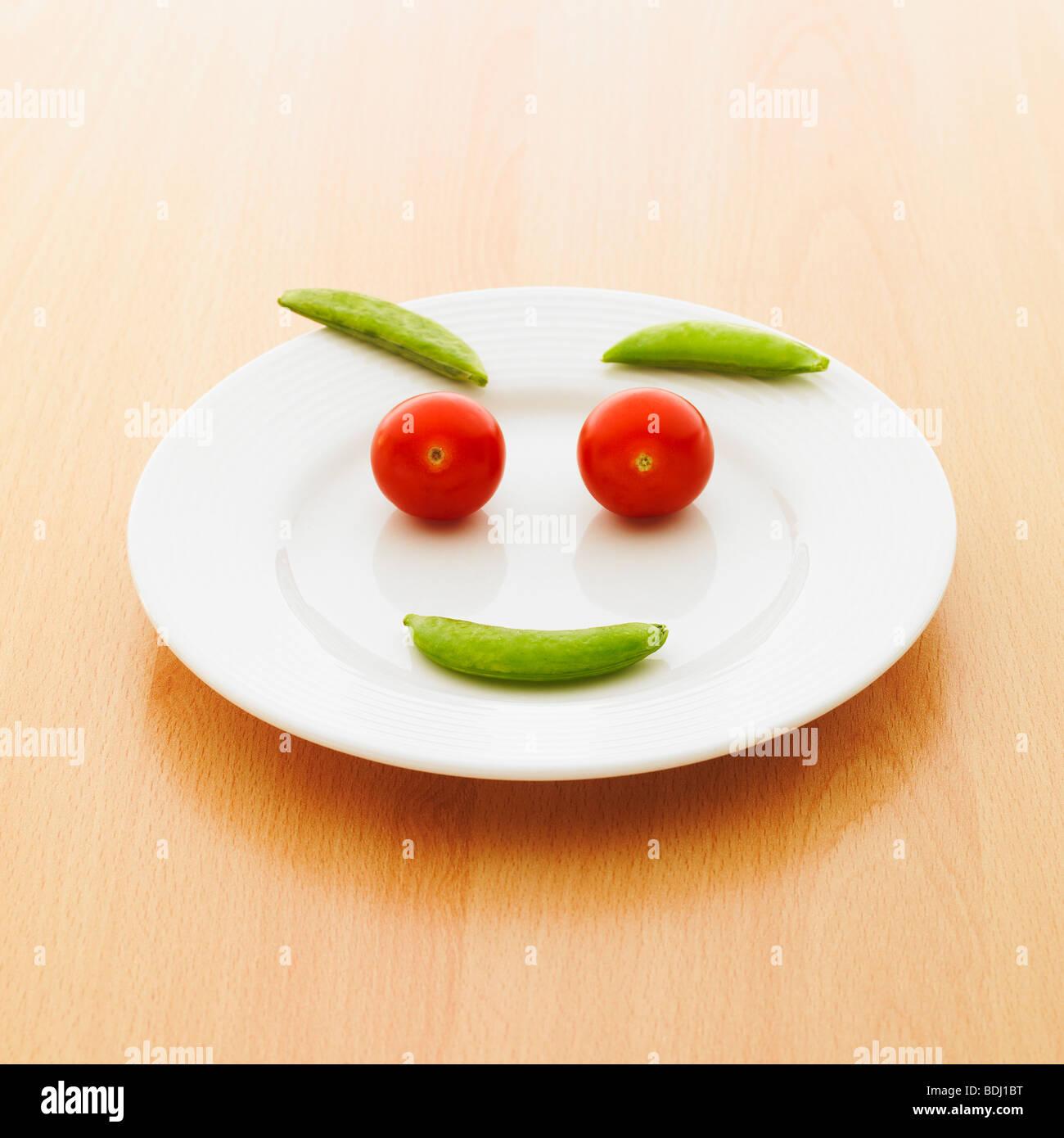 Une assiette de tomates cerises et de pois sugar snap faire un smiley. Photo Stock