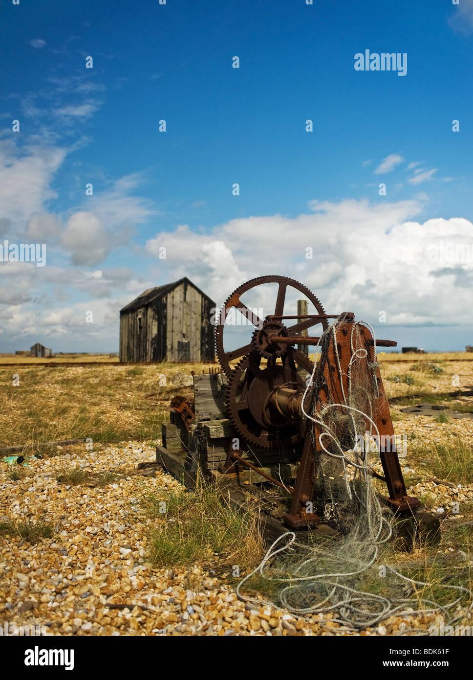 Rusty abandonnés les machines et cabanes de bois sur la plage de galets à Dungeness, dans le Kent. Photo Stock