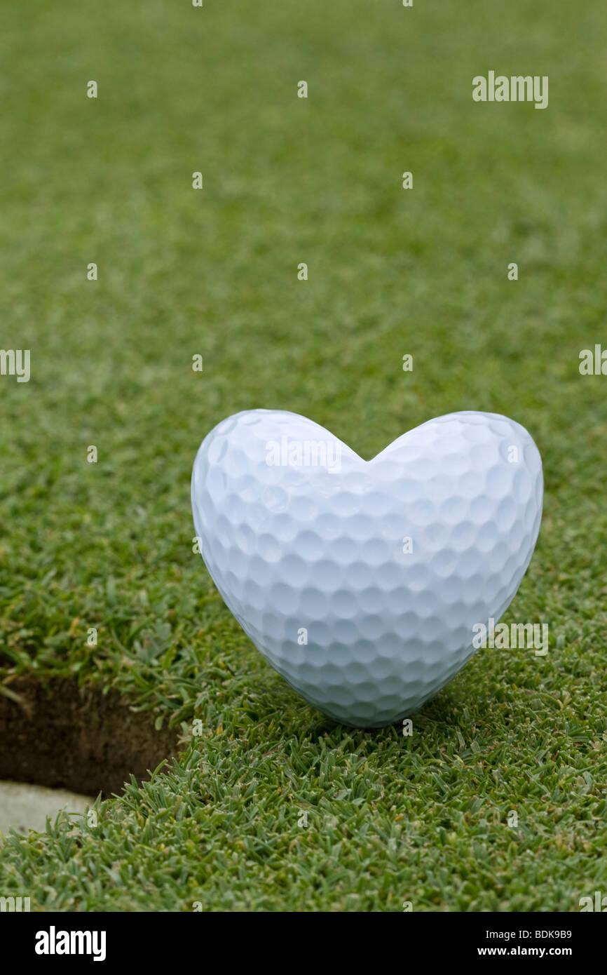 balle de golf en forme de c ur assis c t du trou sur. Black Bedroom Furniture Sets. Home Design Ideas