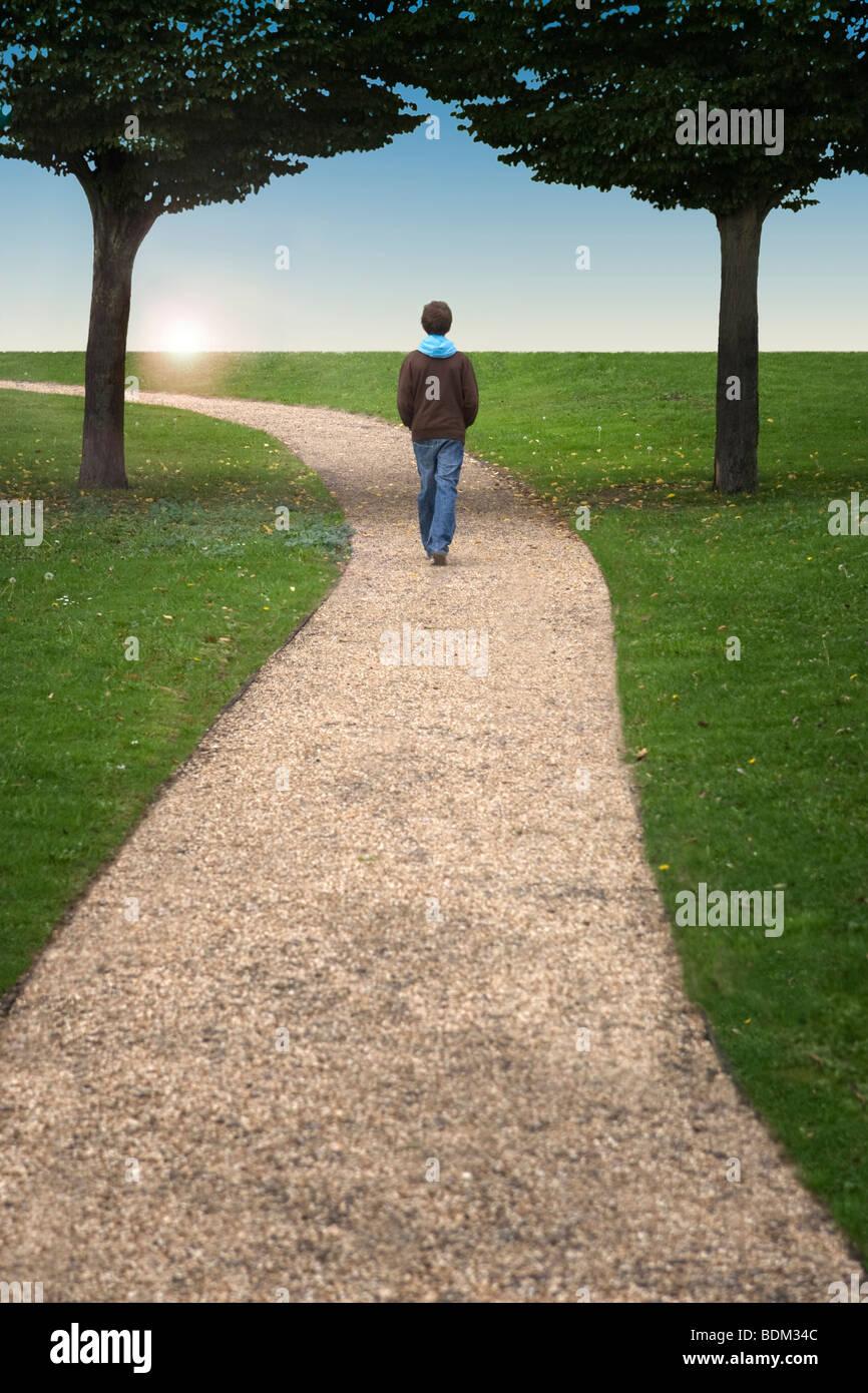 Un garçon marchant le long d'un chemin entre deux arbres en vue d'un coucher de soleil Banque D'Images