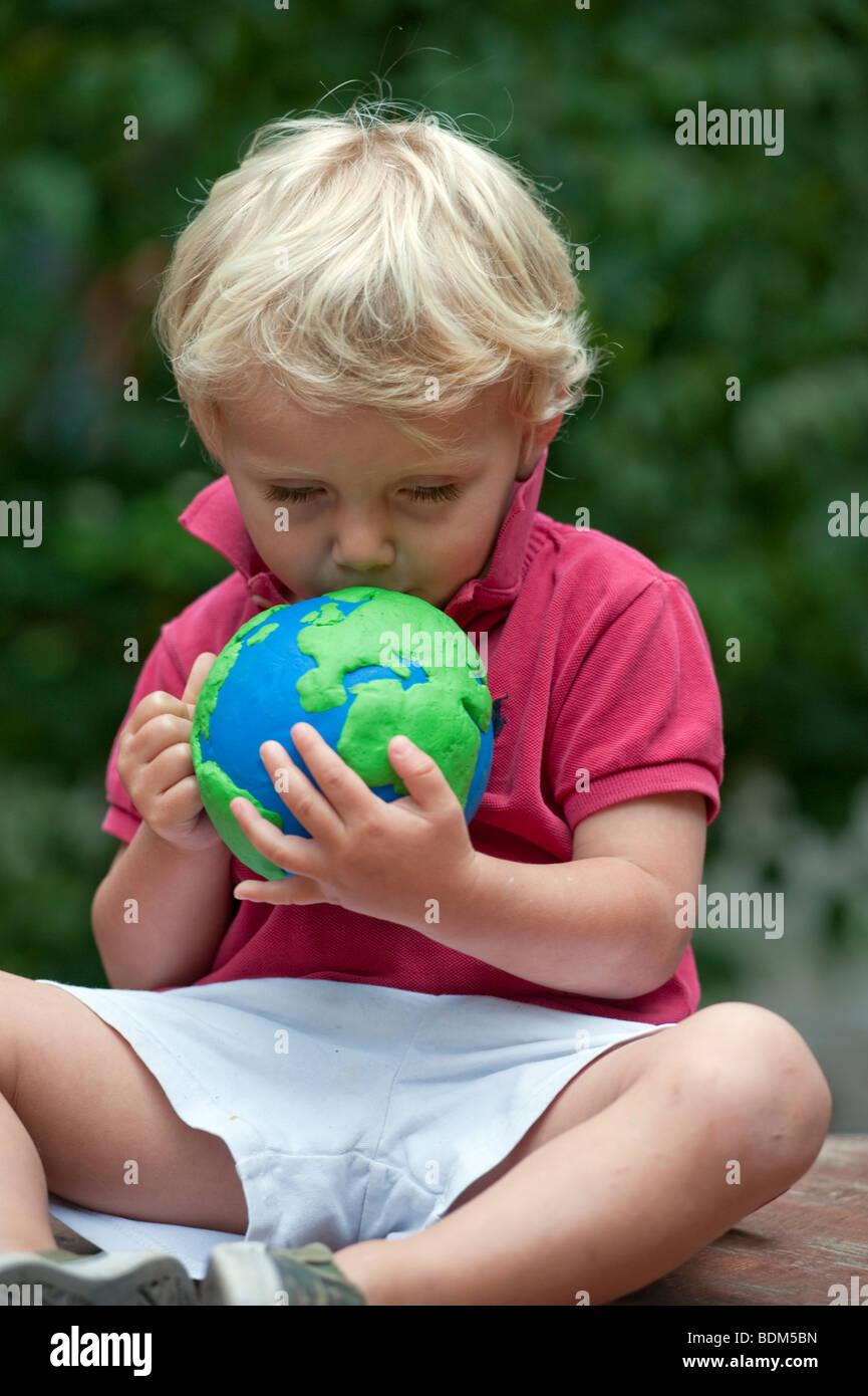 Jeune garçon de câlins et tenant un modèle de la planète Terre Photo Stock