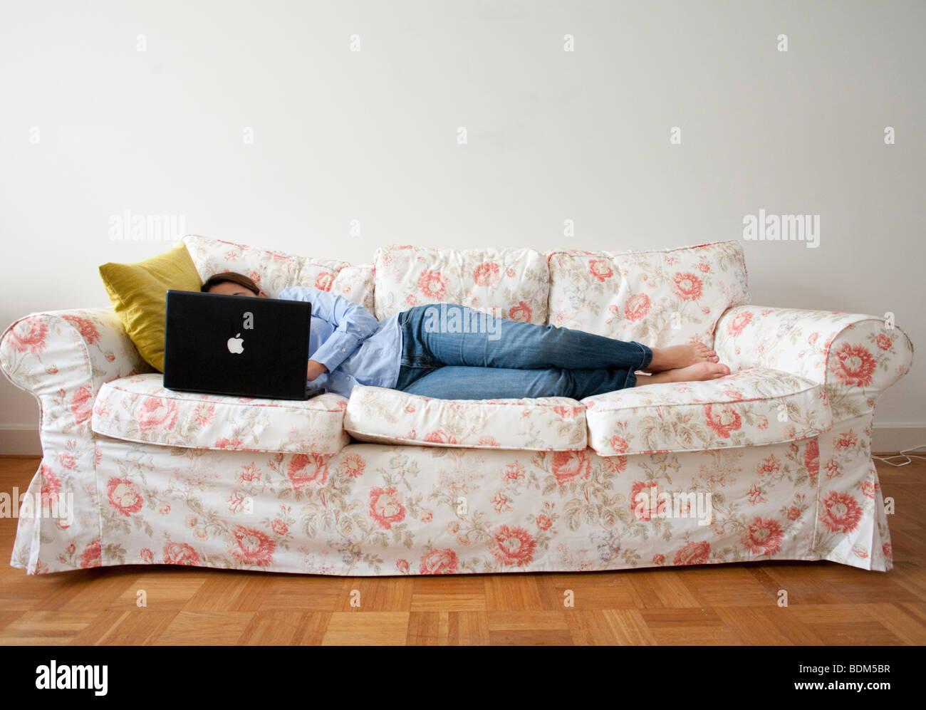 Young woman lying on sofa à la maison en travaillant avec un ordinateur portable Photo Stock