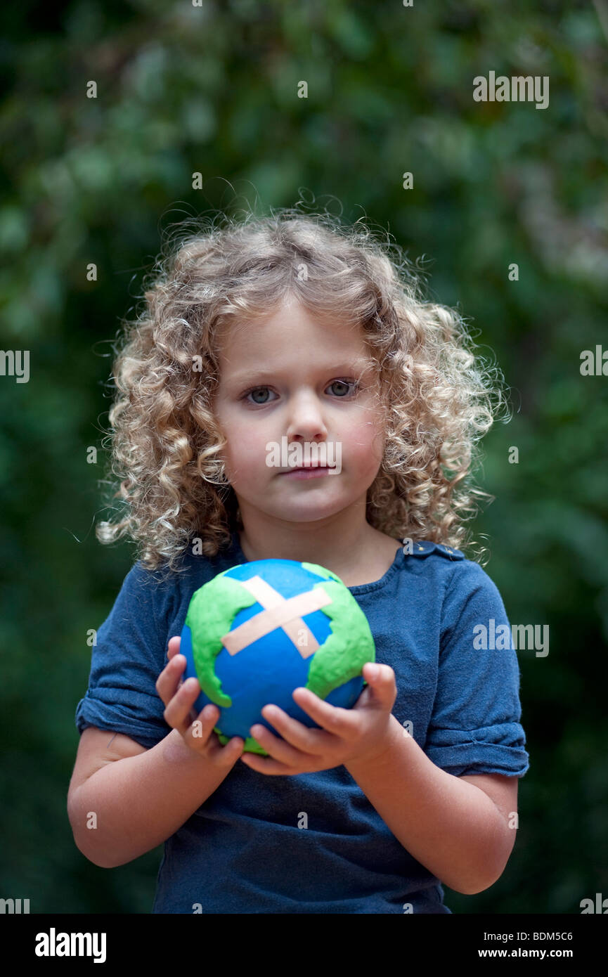 Jeune fille tenant une maquette d'un malade la planète Terre avec une aide de bande attaché Photo Stock