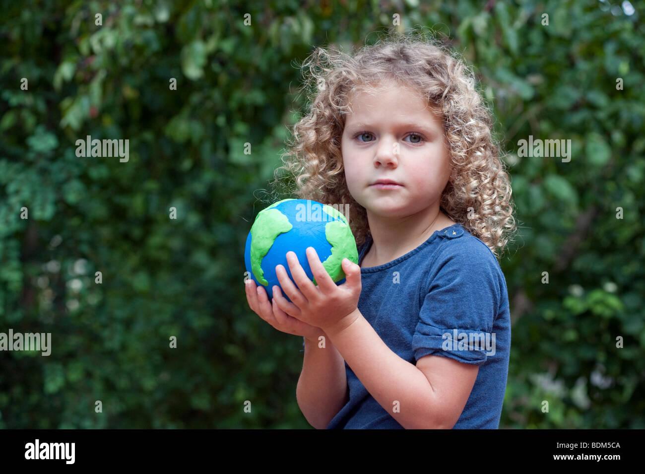 Jeune fille tenant un modèle de la planète Terre Photo Stock