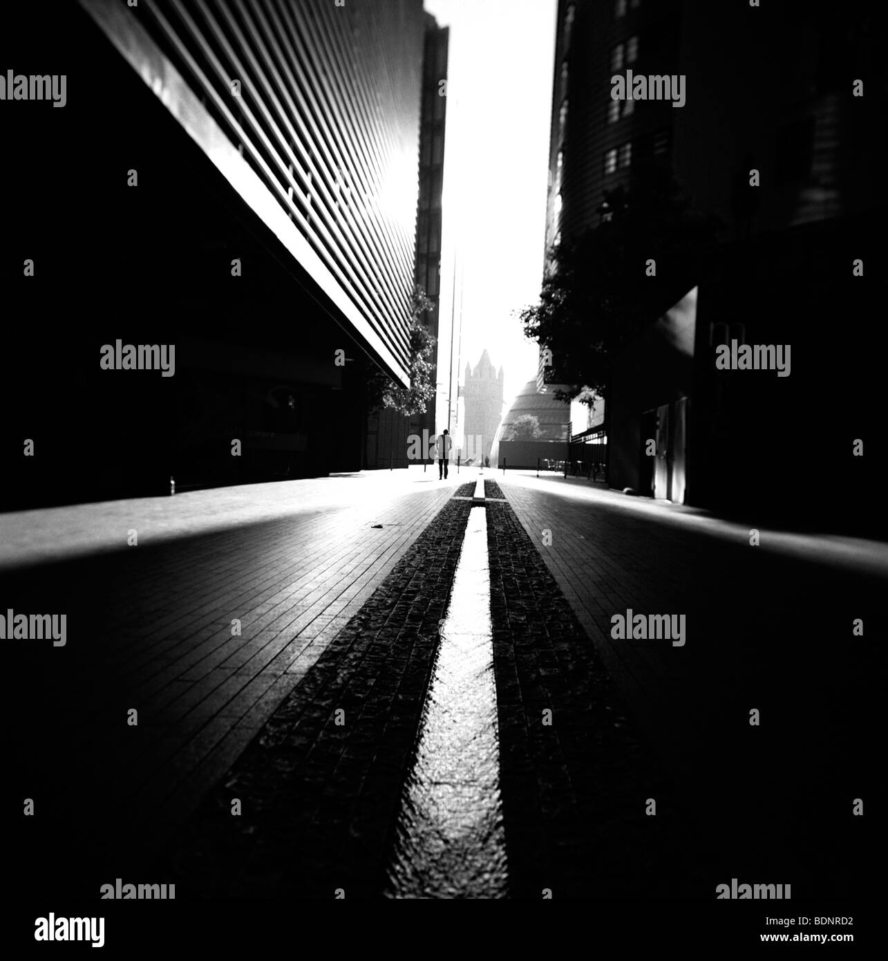 La figure solitaire marchant le long de la rue sombre avec de grands bâtiments London England Photo Stock