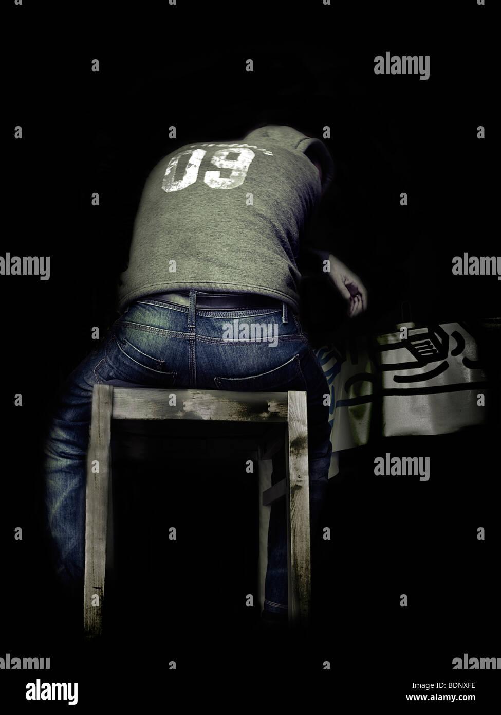 Un jeune homme portant une culotte, assise sur un banc à la dépression Photo Stock