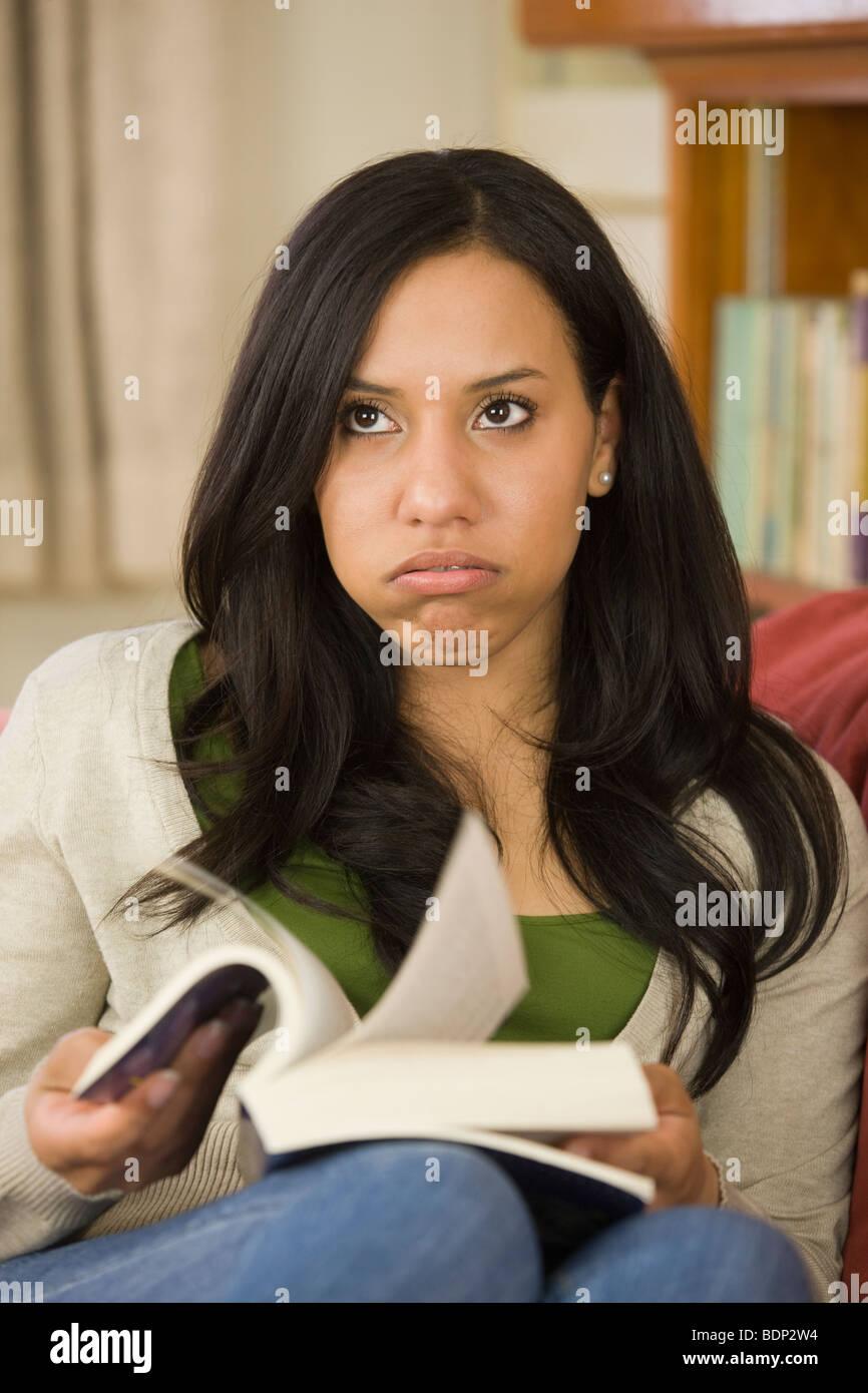 Hispanic woman sitting on a couch et tenant un livre Banque D'Images
