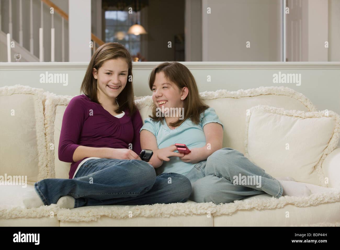 Deux adolescentes assis sur une table et l'utilisation de téléphones mobiles Banque D'Images