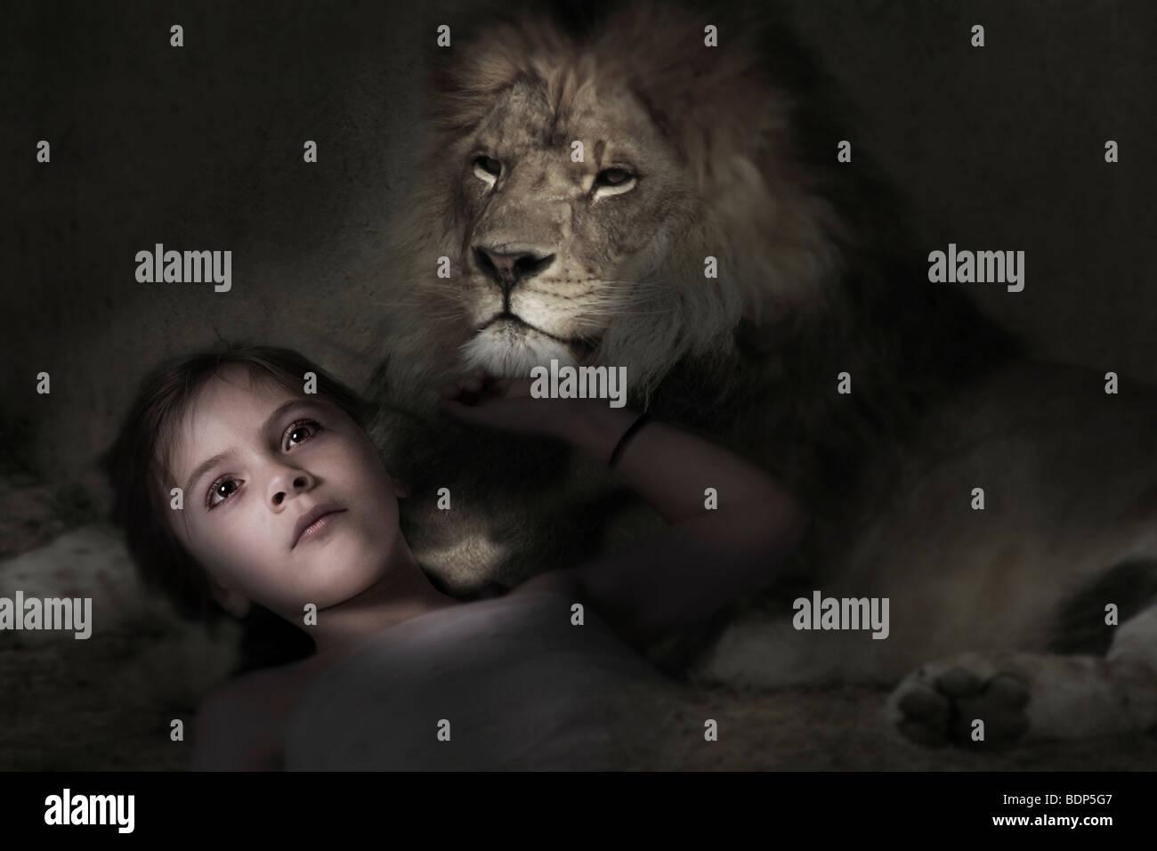 Enfant couché avec un lion dans un endroit sombre et la lumière qui brille sur son visage. Photo Stock