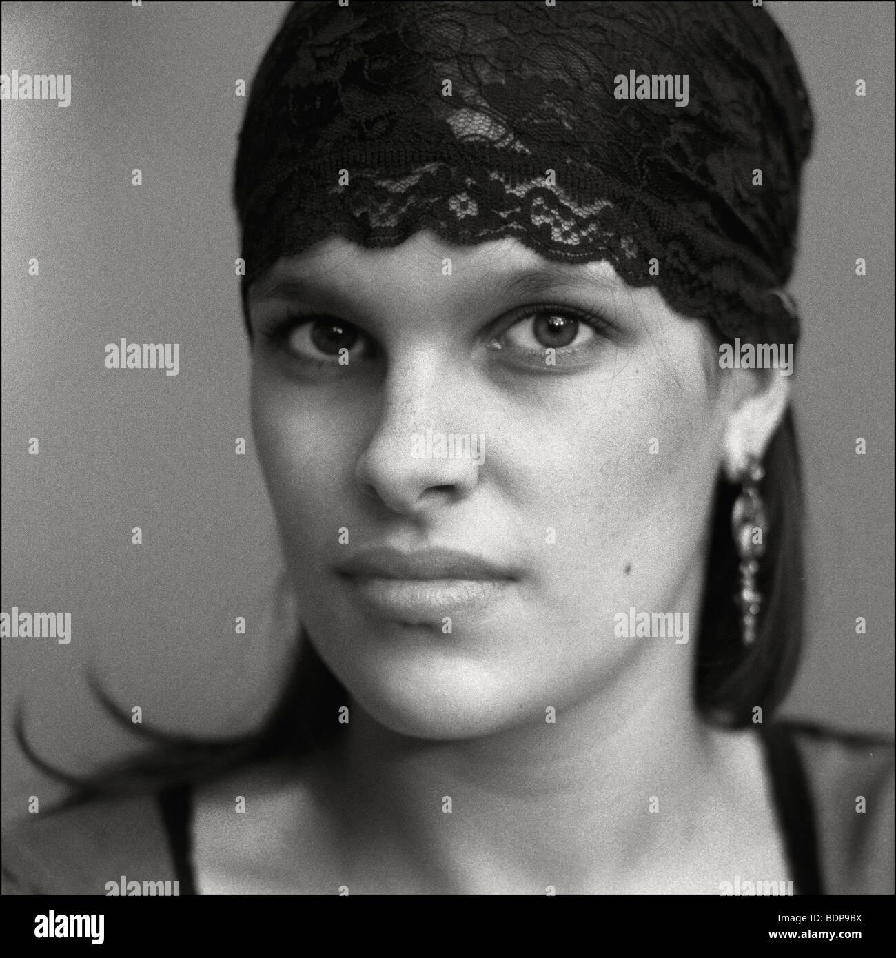 Une femme avec des caractéristiques fortes portant un bandeau de dentelle noire Banque D'Images