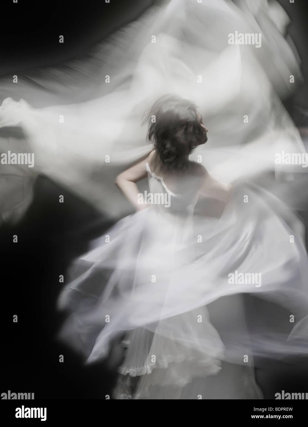 Une jeune femme danser avec une robe blanche Photo Stock