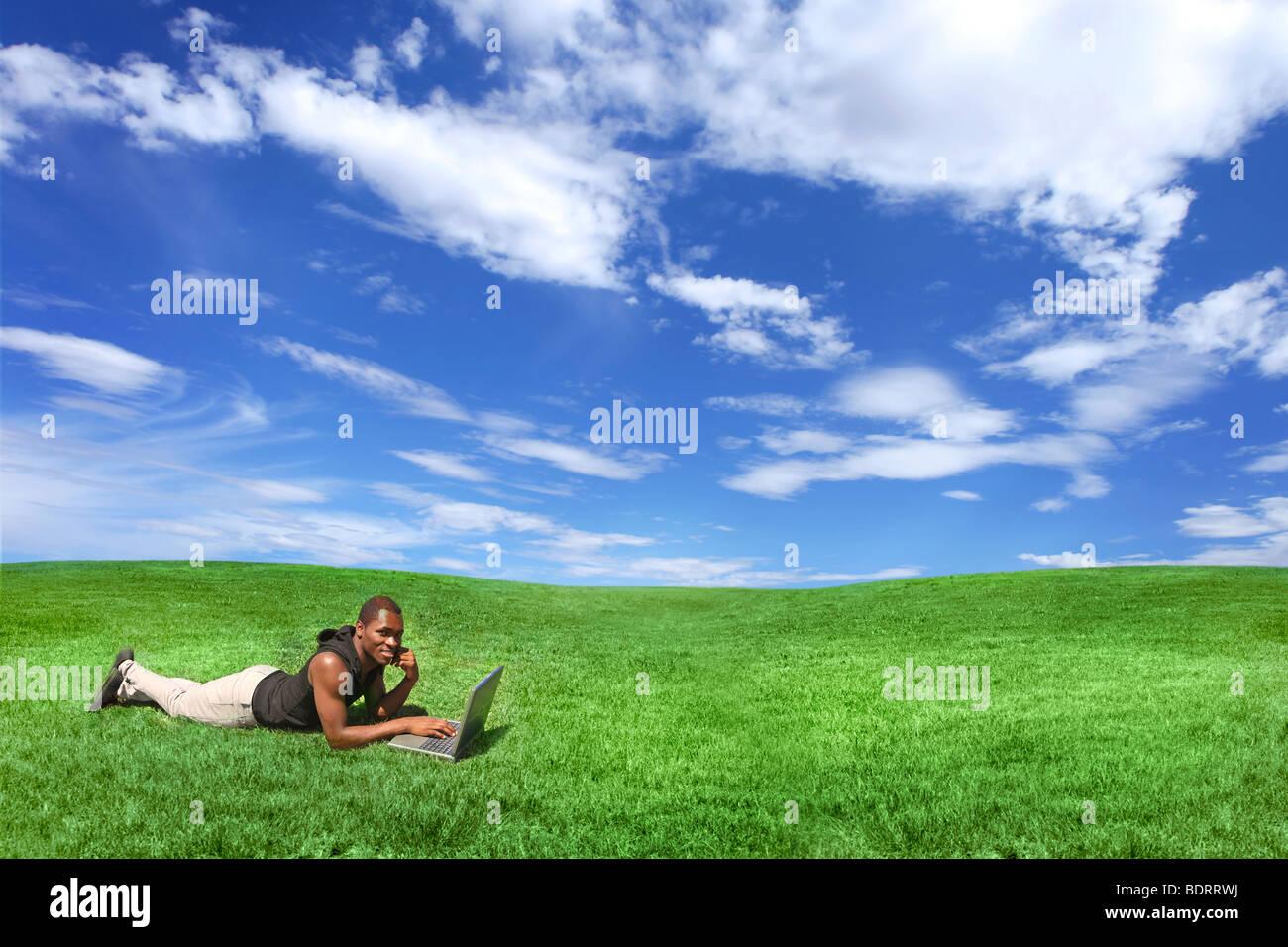 Étudiant travaillant à l'extérieur, sur un ordinateur portable Photo Stock
