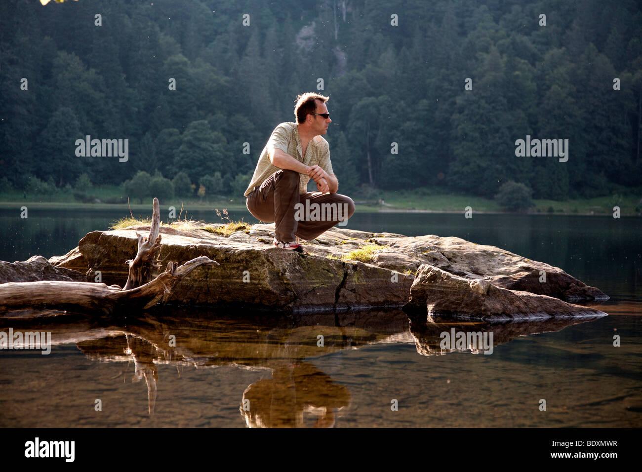 L'homme, mi 40s, accroupie sur un rocher au lac Feldsee dans la Forêt-Noire, Bade-Wurtemberg, Allemagne, Europe Banque D'Images
