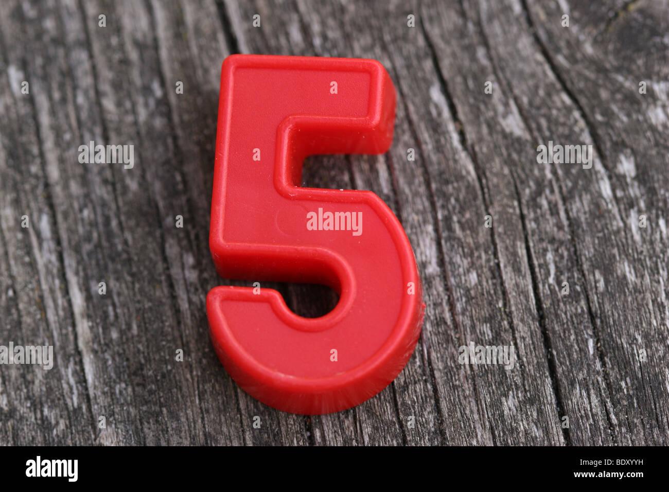 Magnétique rouge numéro cinq sur bois Photo Stock