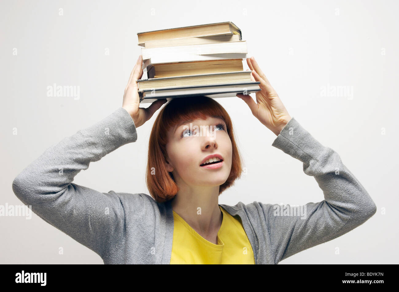 Woman balancing books on head Banque D'Images