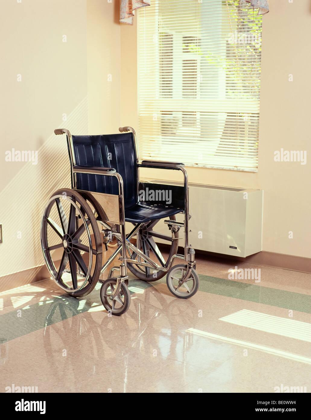 Assis en fauteuil roulant vide par fenêtre Banque D'Images