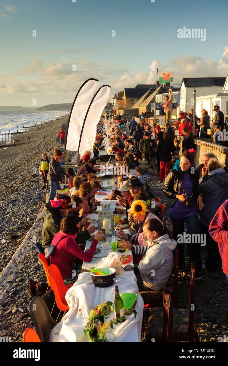 Des gens assis à des tables à l'assemblée annuelle le dîner en plein air sur la plage, soirée d'été, Borth, village Banque D'Images