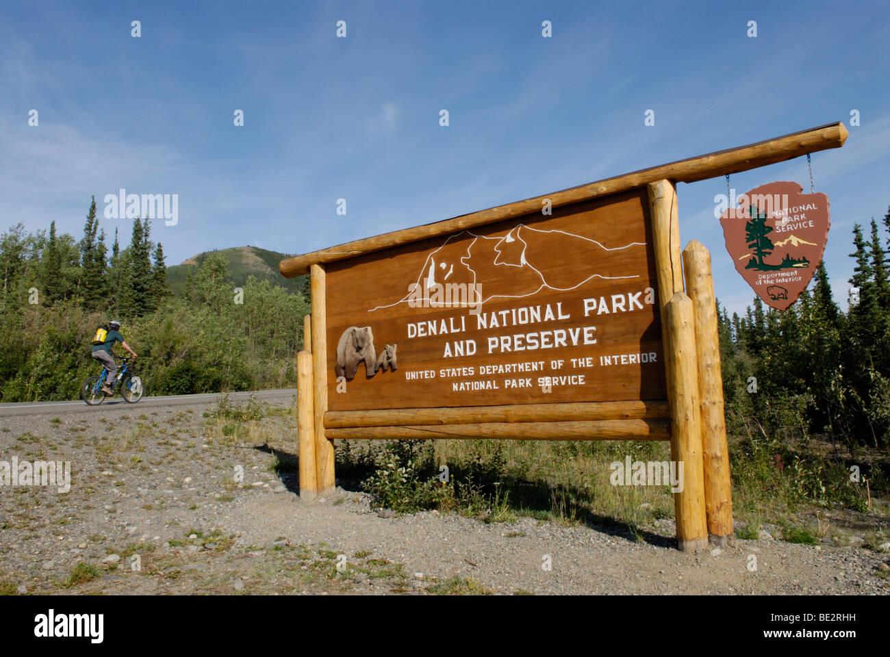 Panneau d'entrée du parc national de Denali avec cyclist Photo Stock