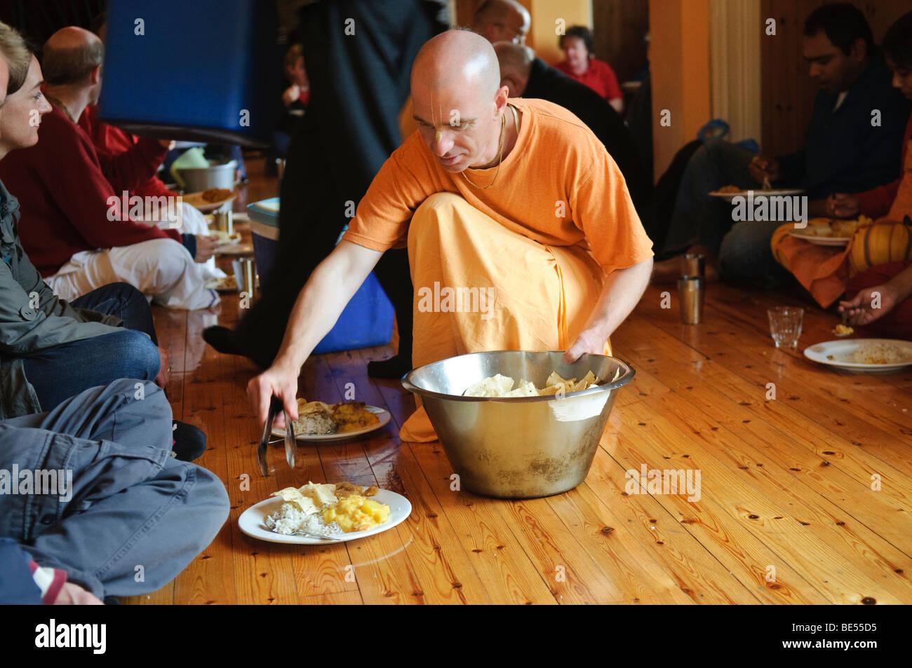 Hare Krishna disciple, habillé en robe safran, orange sert de la nourriture à un festin végétarien dans une chambre du temple Banque D'Images