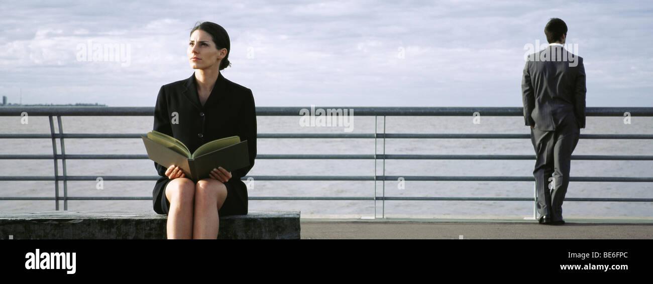 Businesswoman on bench at waterfront avec livre ouvert sur les genoux, l'homme au garde-fous à la vue à Photo Stock