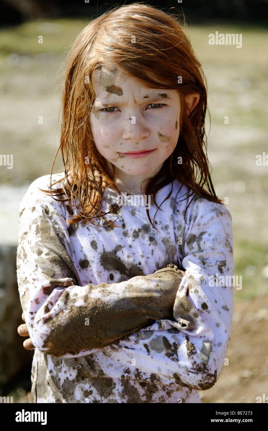 Enfant totalement couvert de boue, sale, sauvage, fille atypique Photo Stock