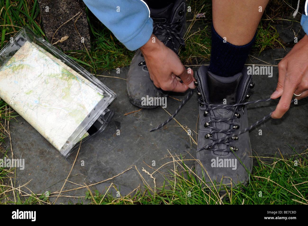 Close up d'une carte et d'une femme d'attacher à lacets avant une randonnée dans la région du Lake District, Cumbria. United Kingdom. Banque D'Images