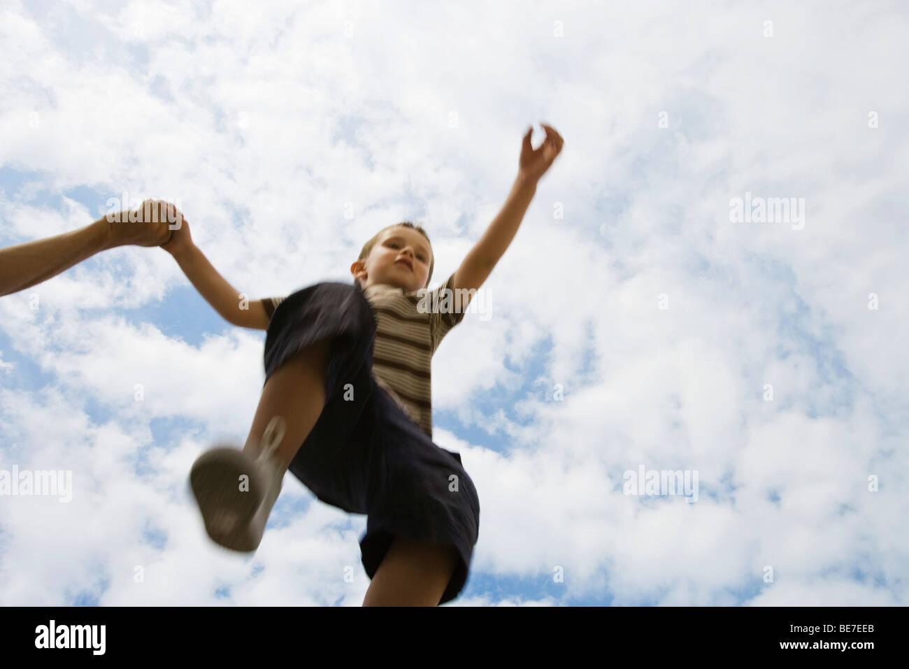 Boy holding mains adultes, sauter dans les airs, low angle view Banque D'Images