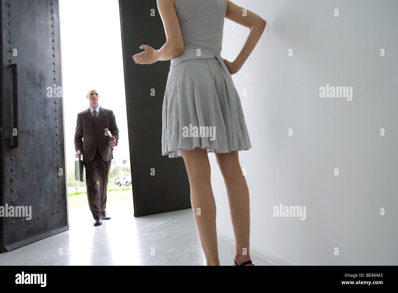 Man Walking through doorway, woman waiting with hand on hip en premier plan Banque D'Images
