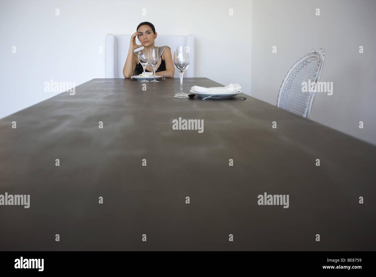 Femme assise seule à la table pour deux, holding head Photo Stock