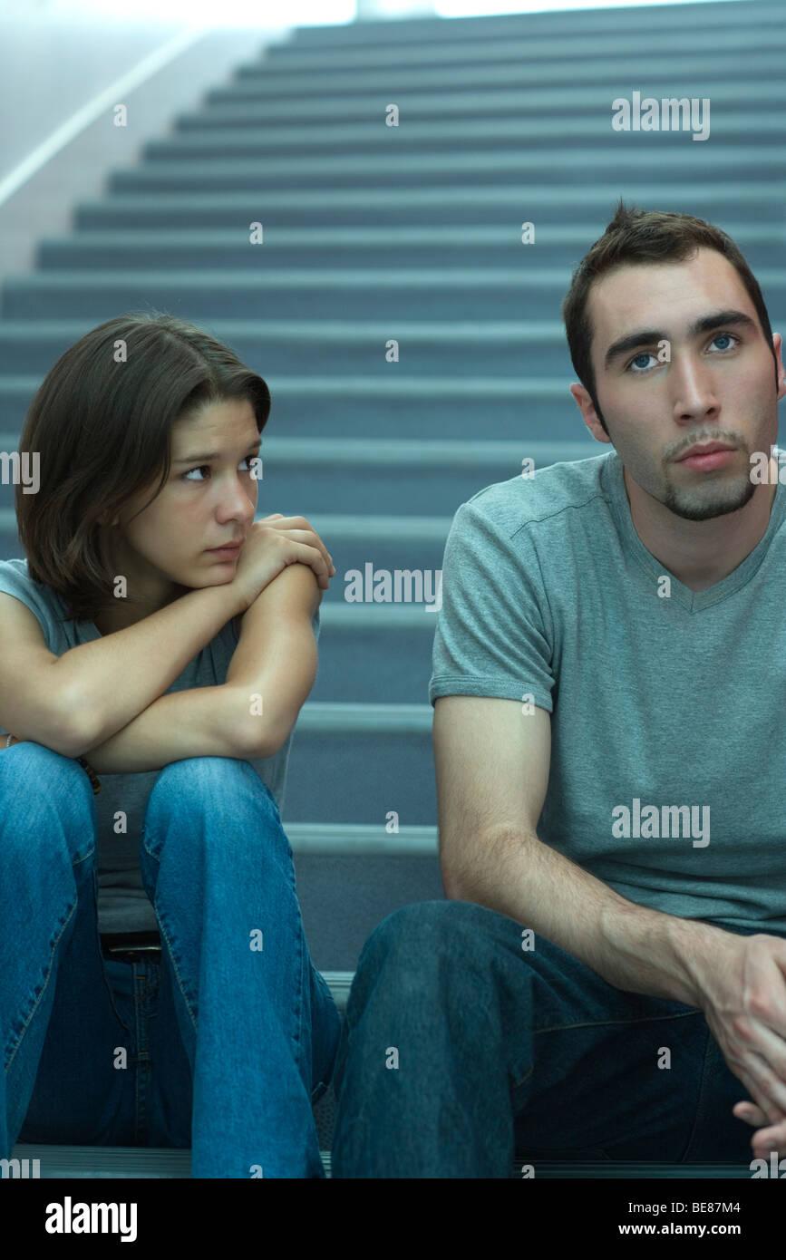 Jeune couple assis côte à côte dans les escaliers, l'homme à la femme, regardant avec inquiétude Banque D'Images