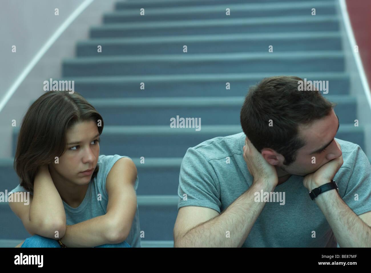 Young couple sitting on stairs, man holding head et à l'écart, regardant femme Banque D'Images