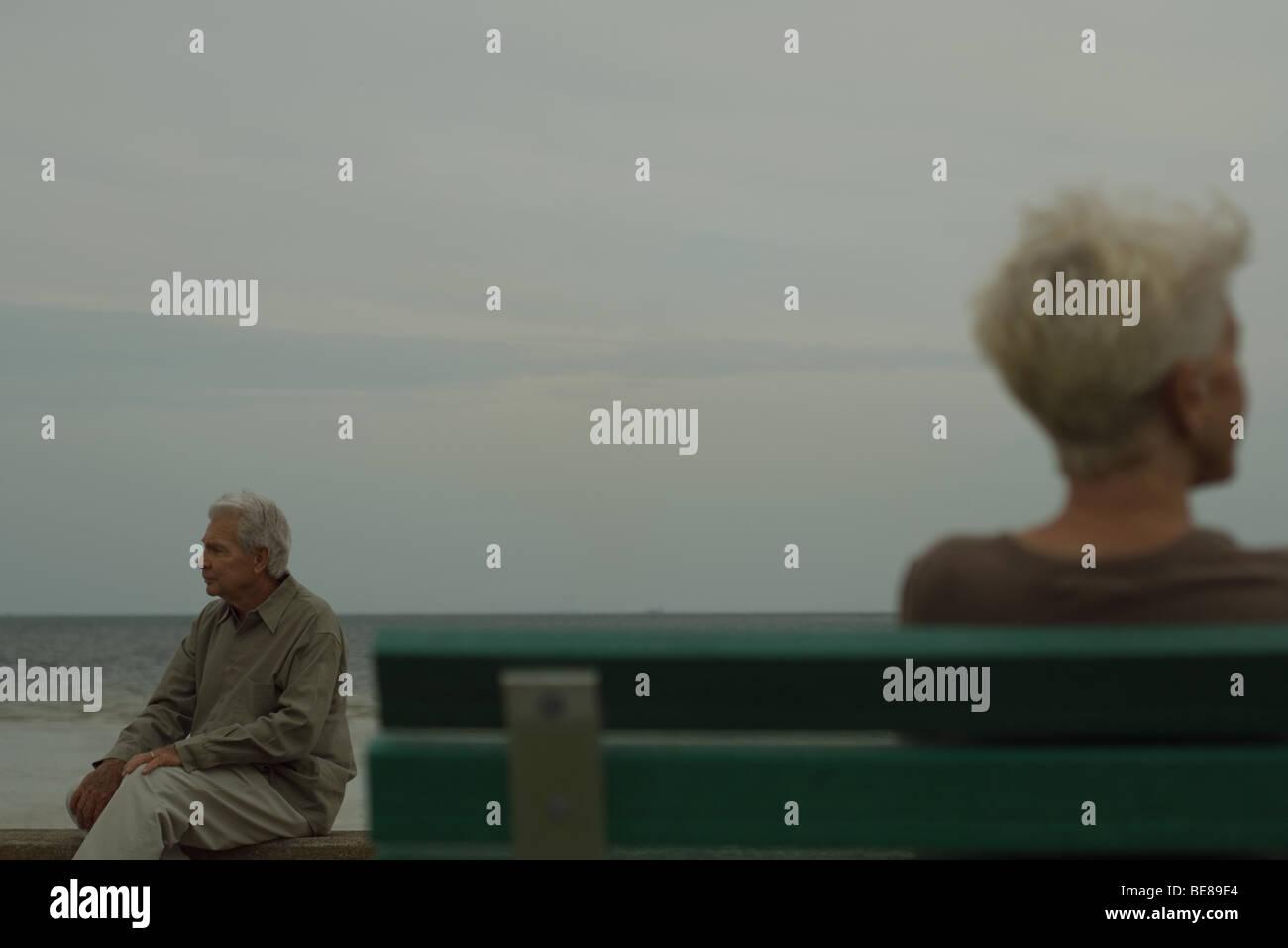 Senior man sitting on bench, à l'écart, senior woman in foreground Banque D'Images
