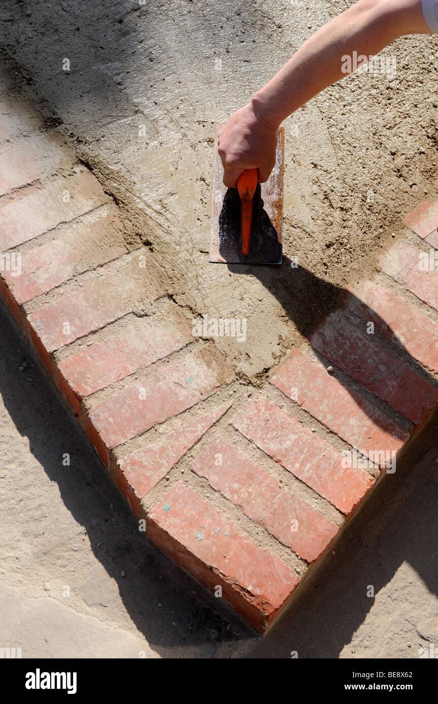 Détail de lissage BÉTON AVEC LES CONSTRUCTEURS D'UN FLOTTEUR DANS LA CONSTRUCTION D'UNE AIRE DE STATIONNEMENT PERMANENT UK Banque D'Images