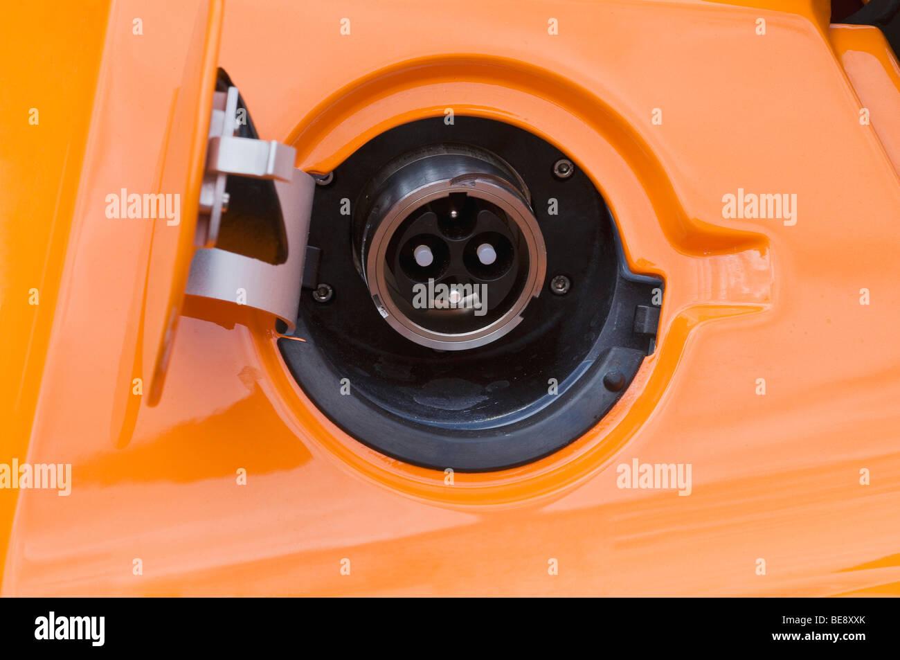 Ouvrir le bouchon du réservoir d'une voiture électrique, prise d'orange Banque D'Images