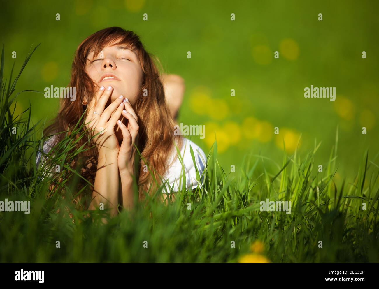 Young woman lying on grass. Shallow dof. Photo Stock