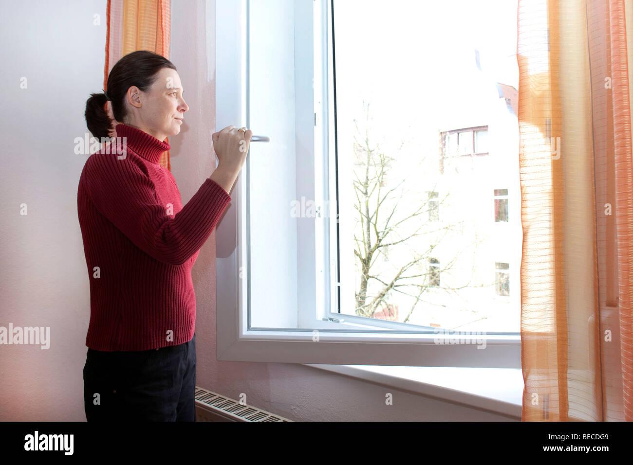 Une jeune femme diffusant son appartement Photo Stock