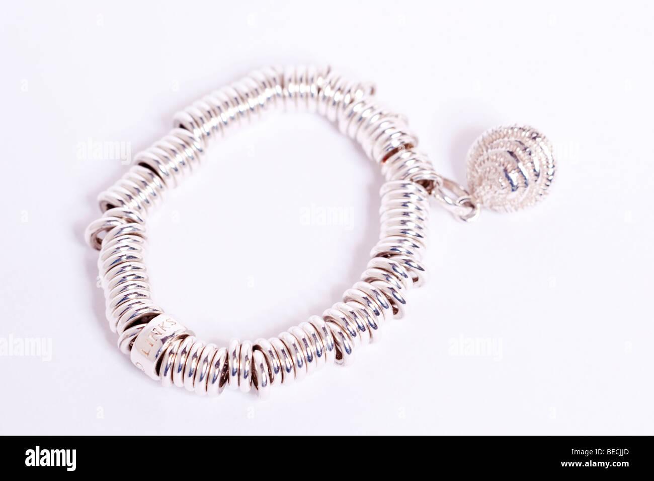 A womans Silver Links of London sweetie bracelet charme sur un fond blanc Banque D'Images