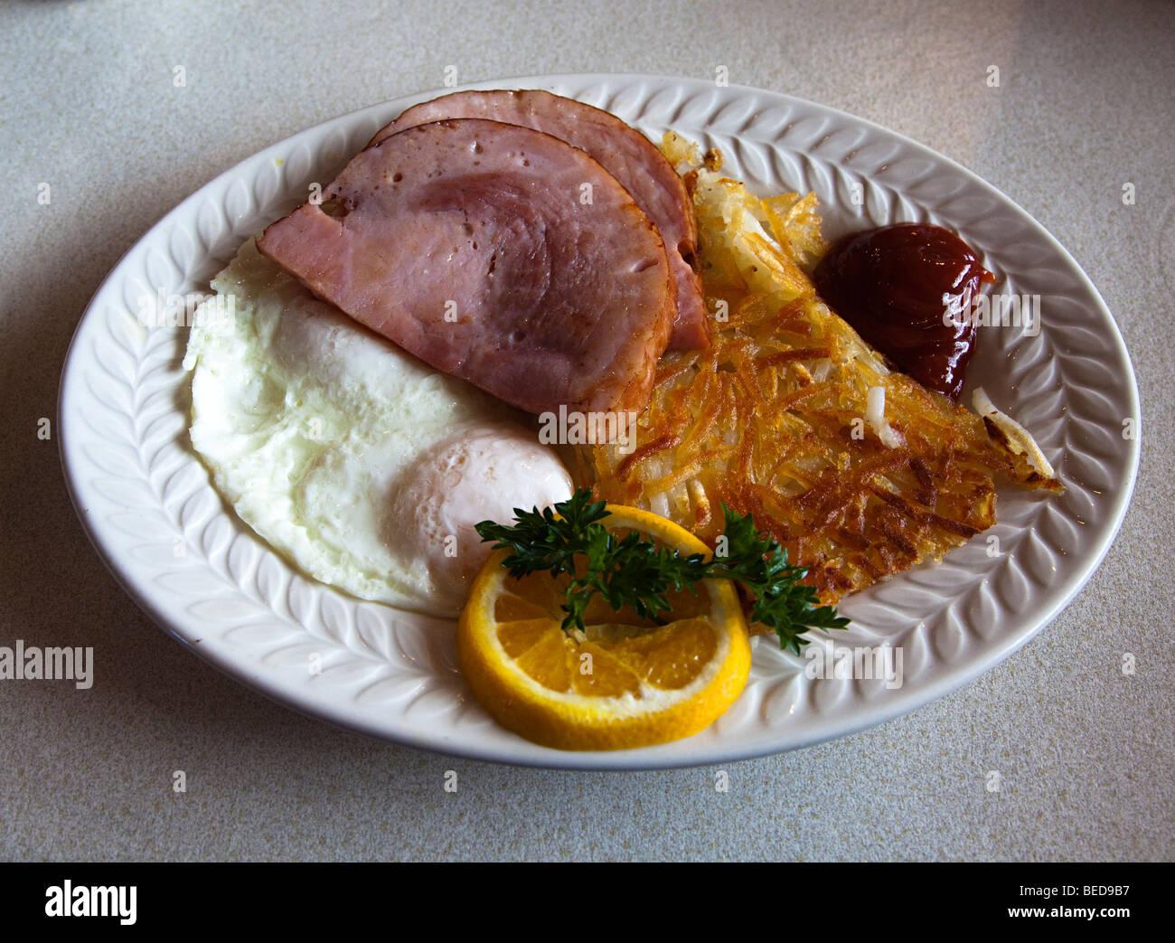 Petit-déjeuner en salle à manger avec des oeufs au plat jambon hash browns orange et ketchup USA Photo Stock